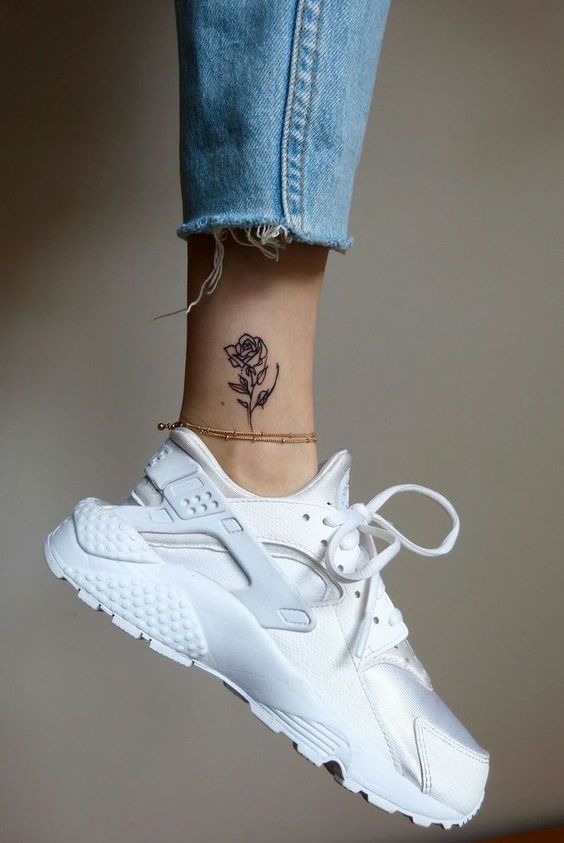 Beautiful black rose tattoo on an ankle
