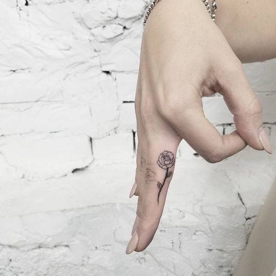Small black rose tattoo on the finger
