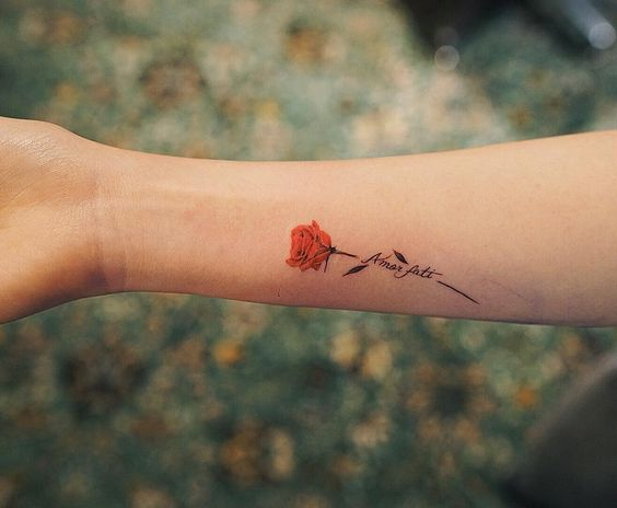 Small red rose tattoo with words Amor Fati
