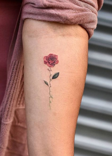 Small rose tattoo with words on inner forearm
