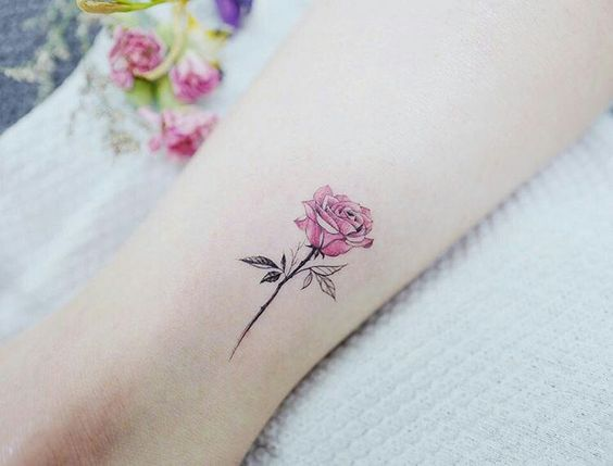 Watercolor style pink Rose Tattoo on a wrist