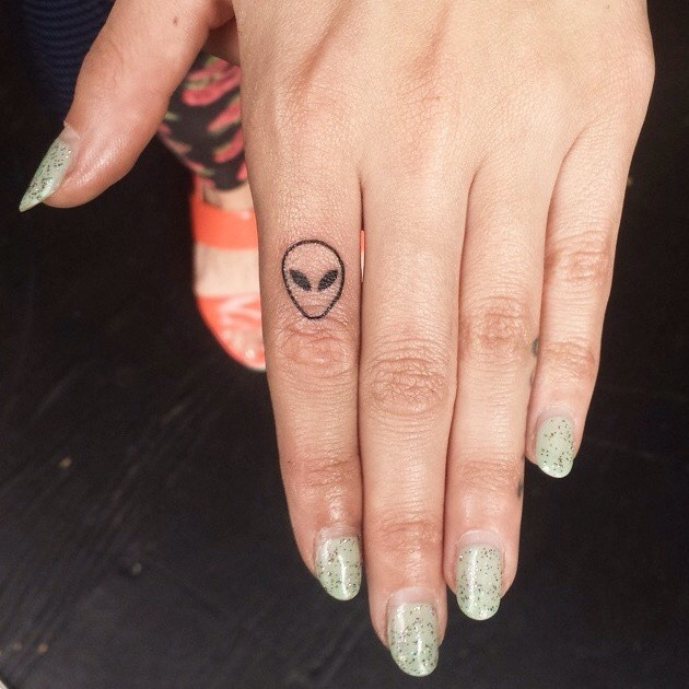 Alien head tattoo on a finger