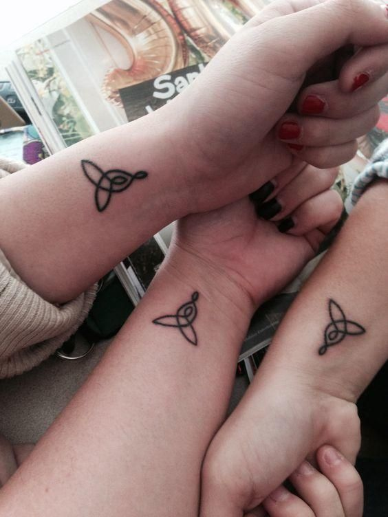 Celtic knot tattoos on wrists for sisters