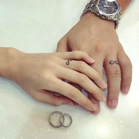Infinity symbol tattoos on fingers