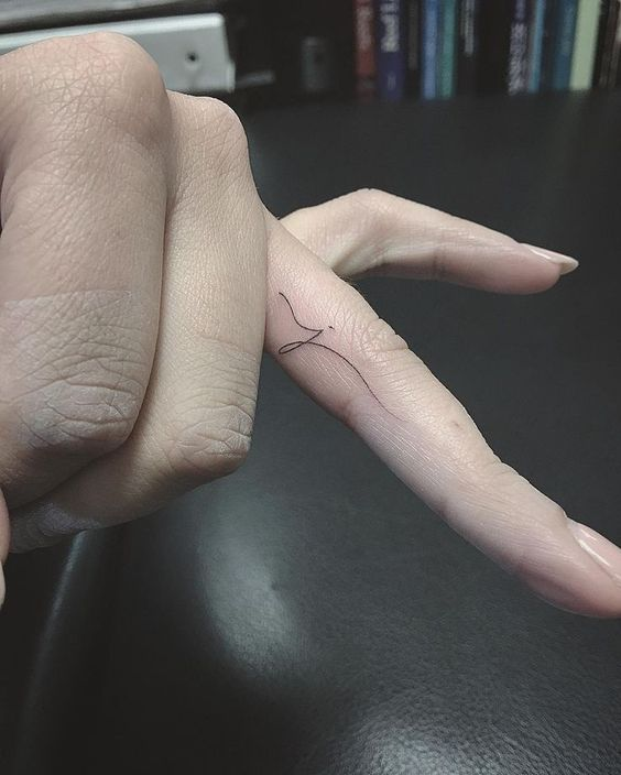 Initial tattoo on a ring finger