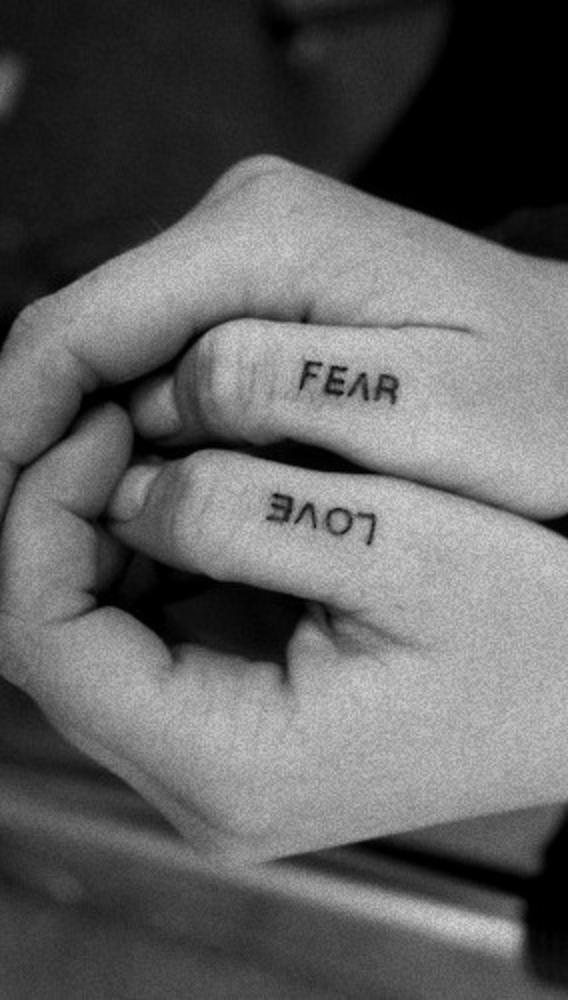 Love and fear tattoo on a fingers