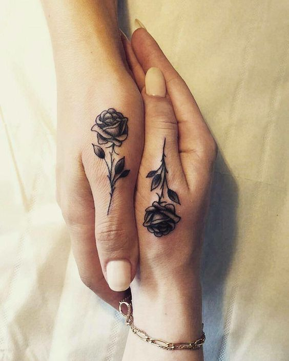 Matching roses tattoo on hands