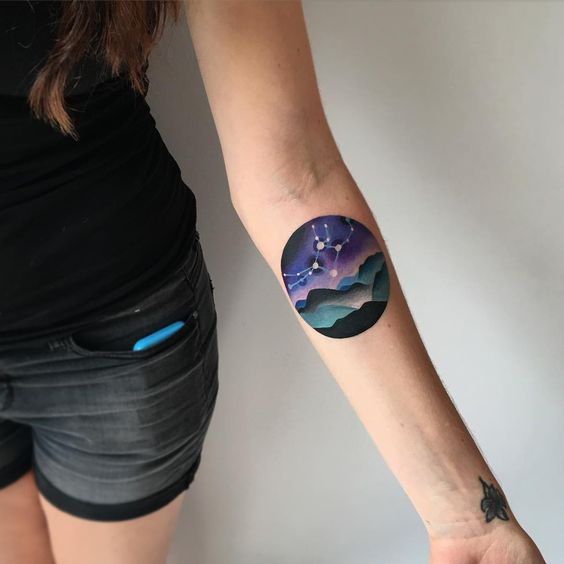 Mountain and constellation tattoo on the inner arm