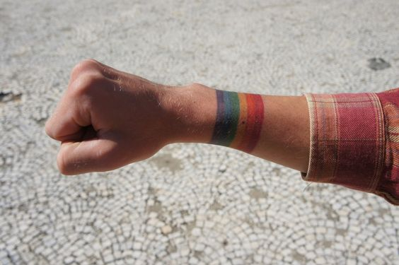 Rainbow armband tattoo symbolizing tolerance by Tattoo Wolff