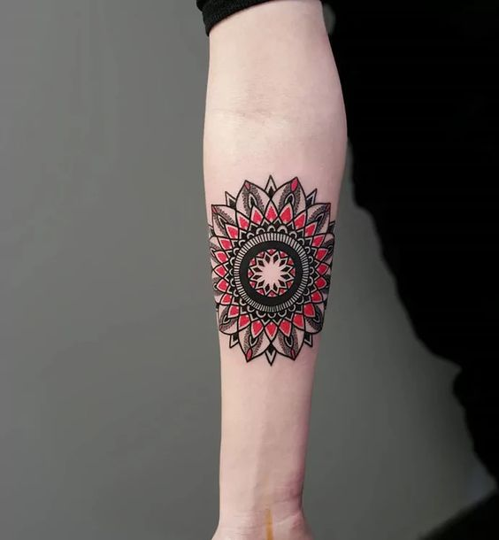 Red and black mandala tattoo on arm