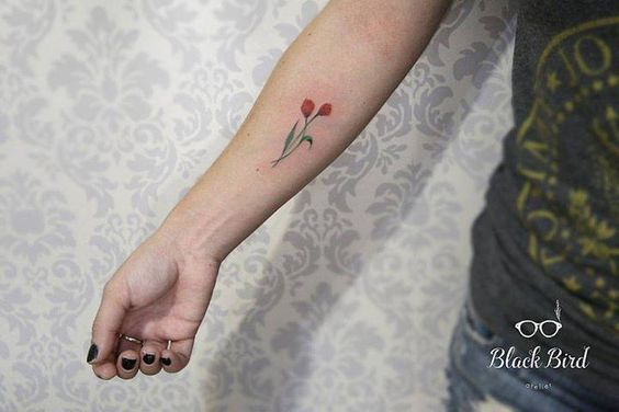 Red tulip tattoo on the right inner forearm