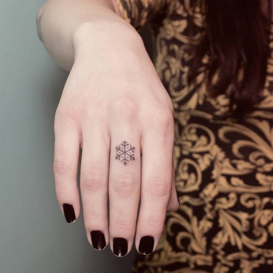 Snowflake tattoo on a middle finger