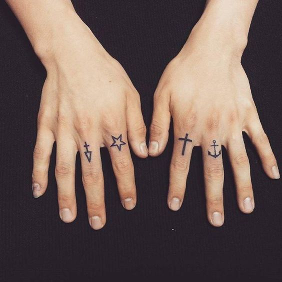 Symbol tattoos on fingers