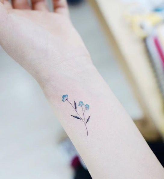 Tiny blue flower tattoo on the wrist