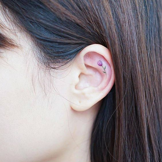 Tiny tulip tattoo on the left ear