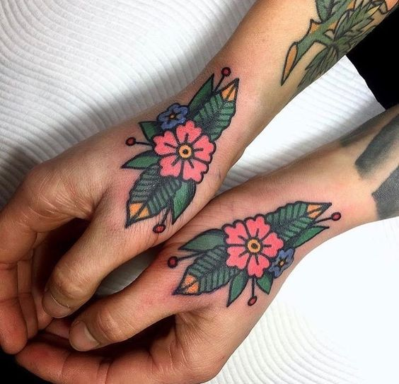 Traditional flower tattoos on both hands by @missquartz