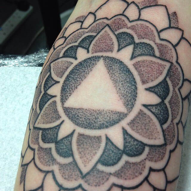 Black and red mandala tattoo with a triangle in the center