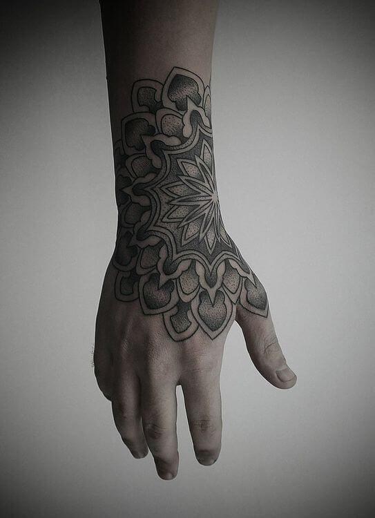 Black dotwork mandala tattoo on the wrist and the hand