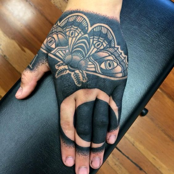 Butterfly and crescent moon tattoo on the hand