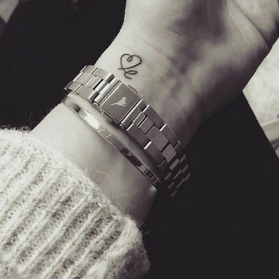 Heart tattoo with a letter on the wrist