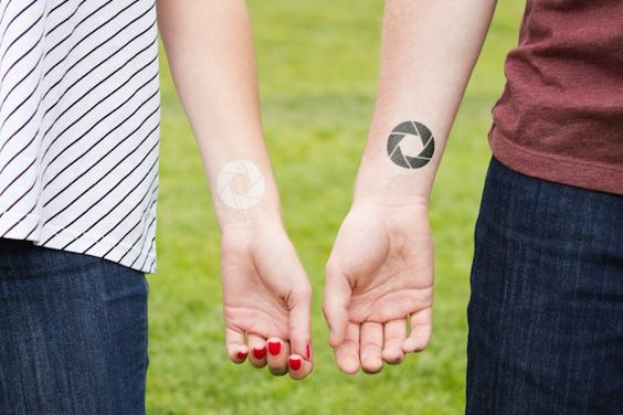 Matching aperture tattoos on the wrists