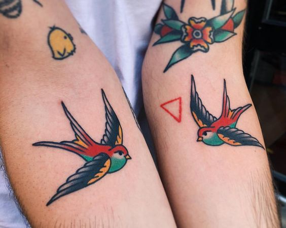 Matching small swallow tattoos on both arms