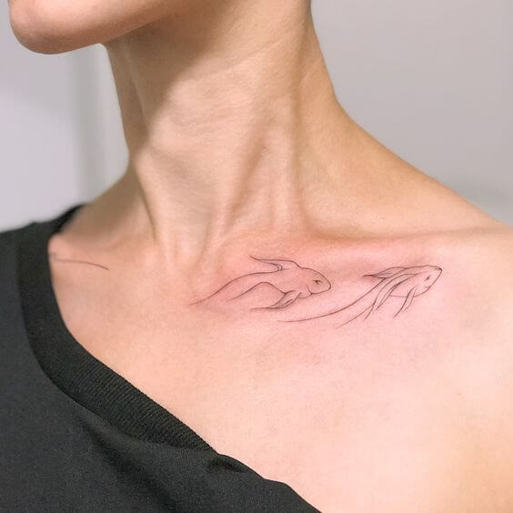 Minimalist fish tattoo on the clavicle