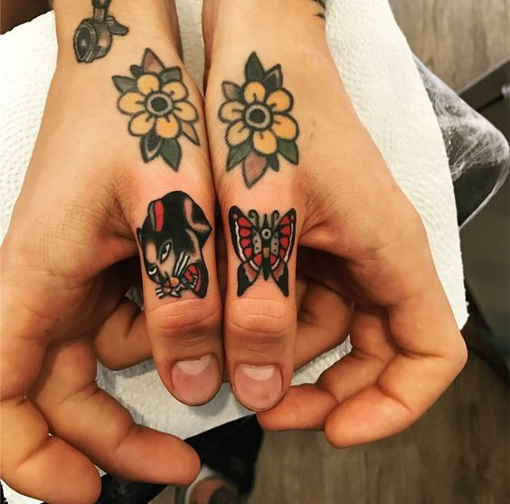 Panther and butterfly tattoos on thumbs