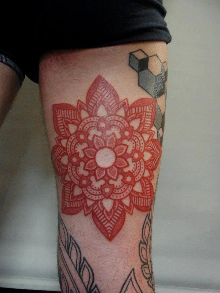 Red mandala tattoo on the thigh