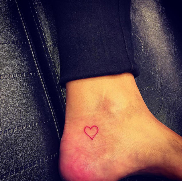 Red outline heart tattoo on the ankle