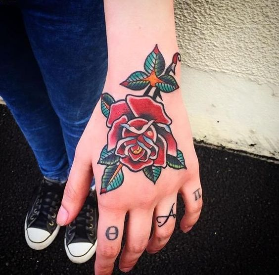 Red rose traditional style tattoo on the hand