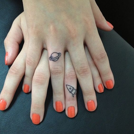 Saturn and small rocket tattoo on the fingers