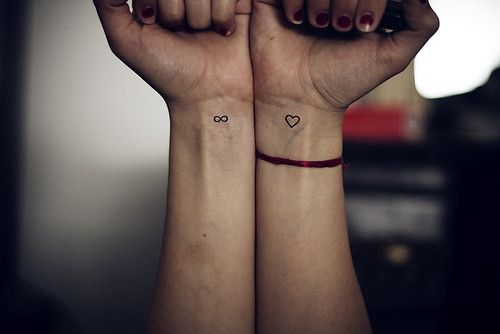 Small heart tattoo and infinity sign on wrists