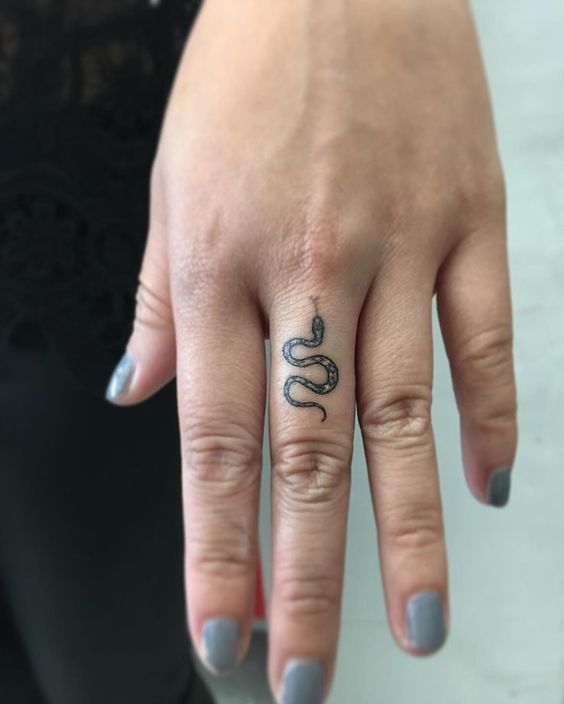 Small snake tattoo on the middle finger