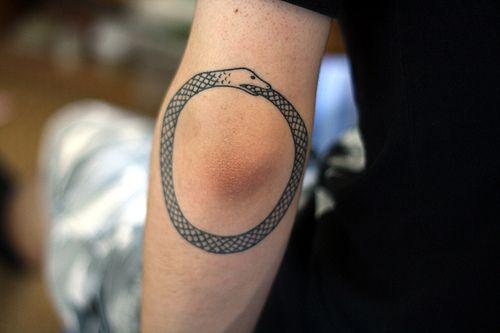 Snake tattoo around the elbow