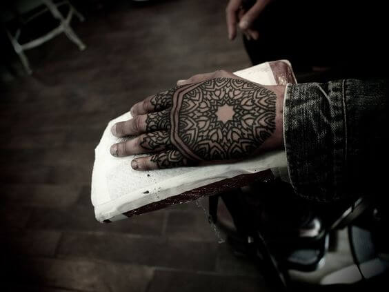 Solid black mandala tattoo on the hand for guys