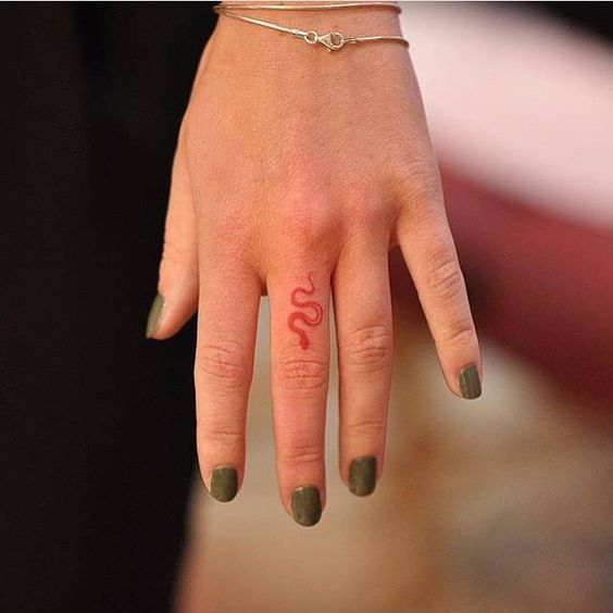 Tiny red snake tattoo on the finger