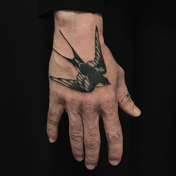 Traditional style swallow tattoo on the hand