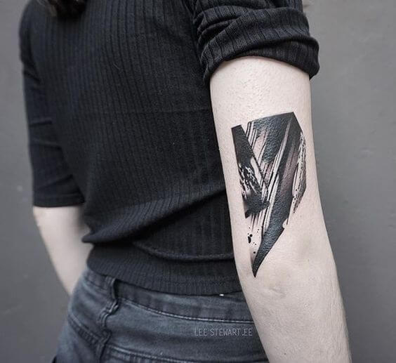 Abstract composition tattoo on the arm above the elbow