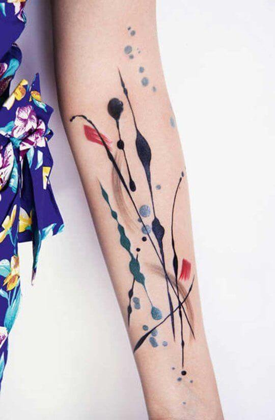 Brush strokes and color splashes tattoo on the arm