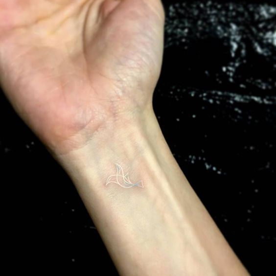 Dove tattoo in white on the wrist