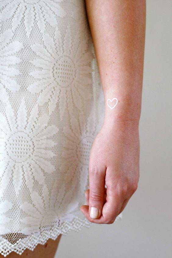 Little white heart tattoo on the wrist