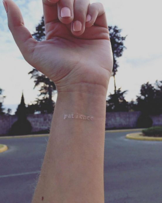 Patience white tattoo on the wrist