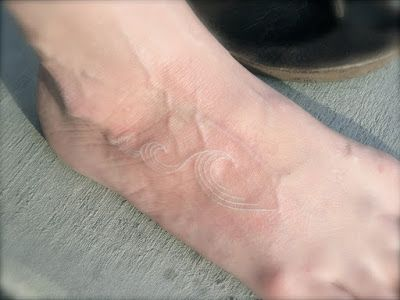 Small white wave tattoo on the foot