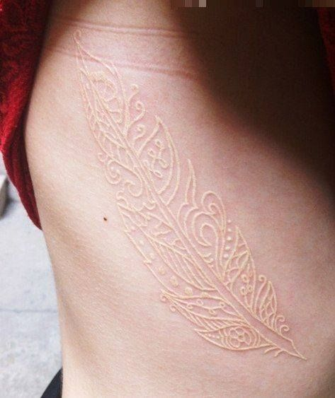 White feather tattoo on the side
