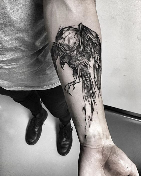 Abstract black raven tattoo on the left inner arm