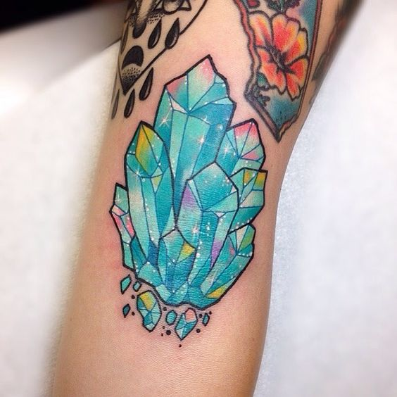 Aquamarine glowing crystal tattoo on the arm