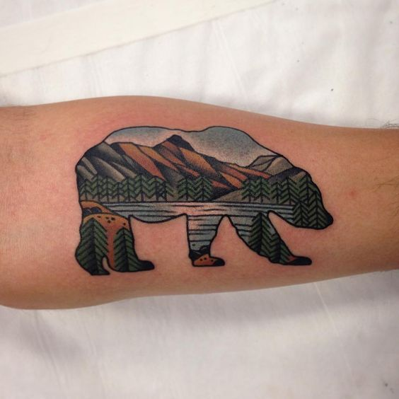 Bear with nature landscape tattoo on the arm