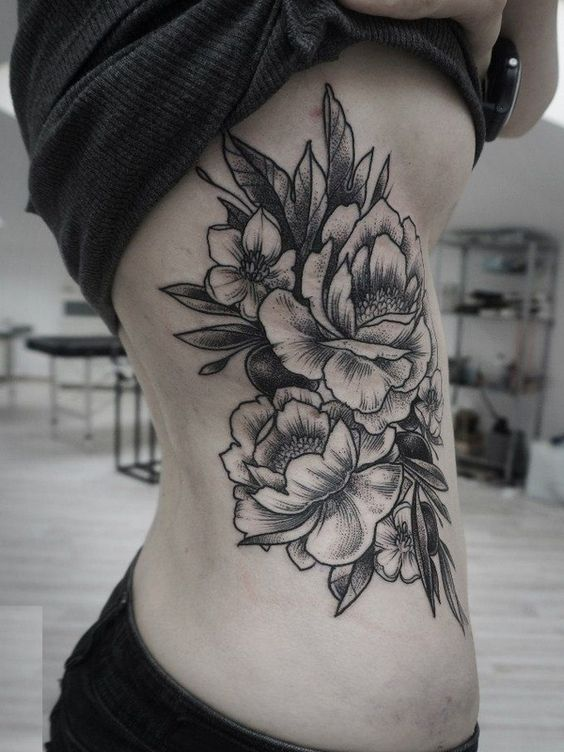 Big black tattoo of a peony on the right side