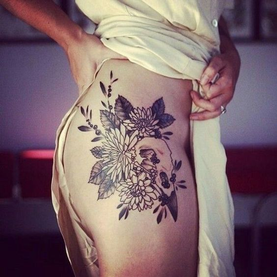 Bird skull in the wildflowers tattoo on the right hip